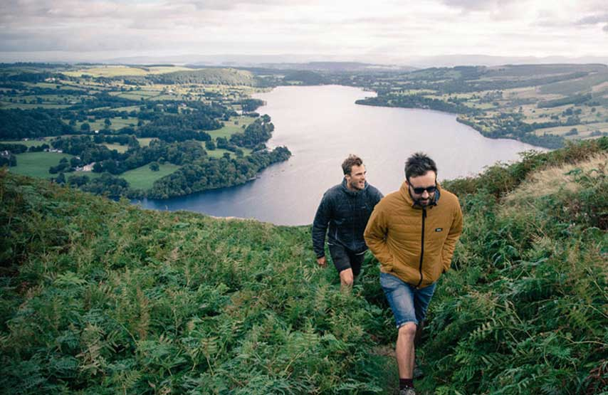 Two friends walking on Hallin Fell with Ullswater behind them