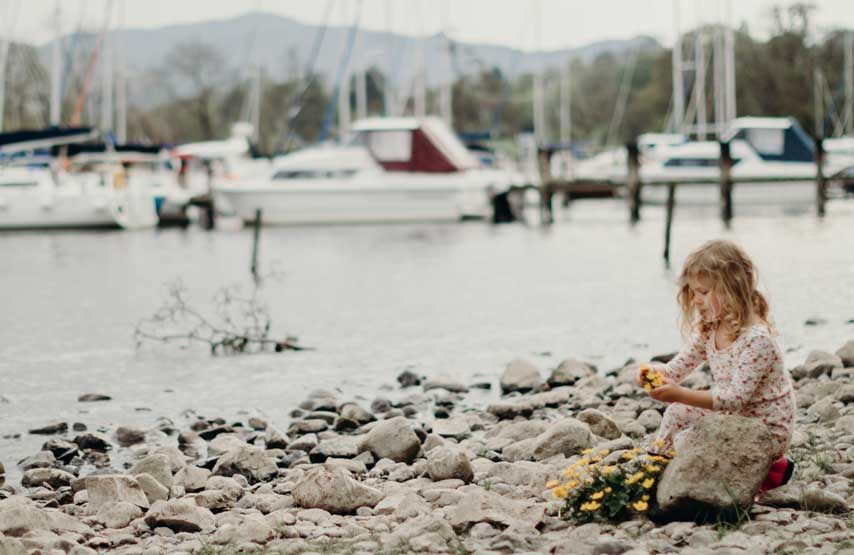 young girl playing on the ullswater shoreline in the lake district UK