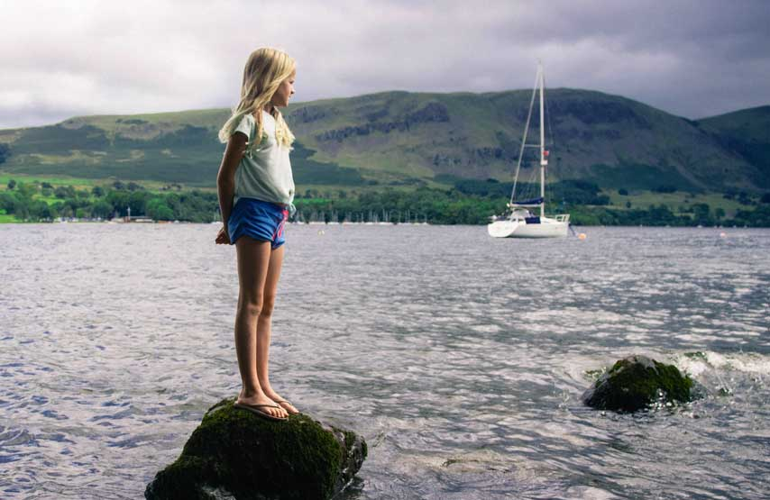 standing on a rock on ullswater with the lake district mountains in the distance