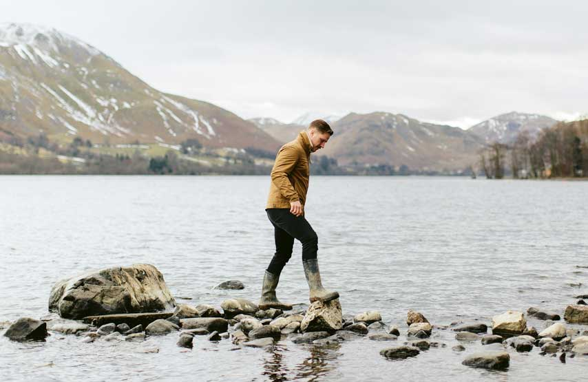 Man walking on stepping stones on the lake shore