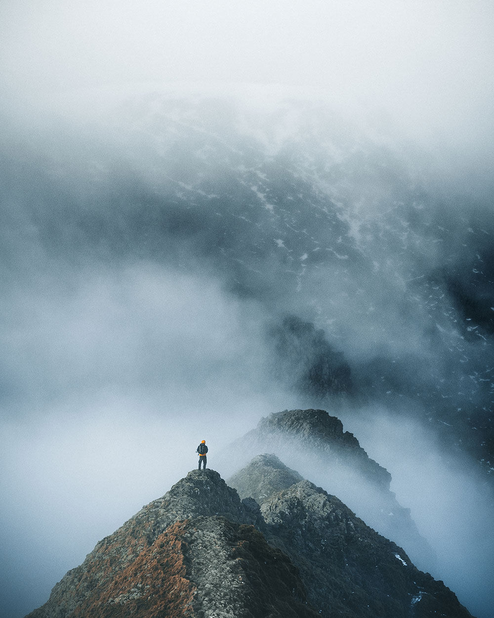 Ryan Lomas stands upon a rugged mountain peak surrounded by clouds