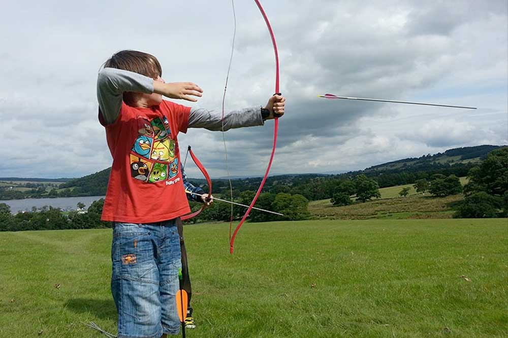 Boy shooting arrow during archery lesson
