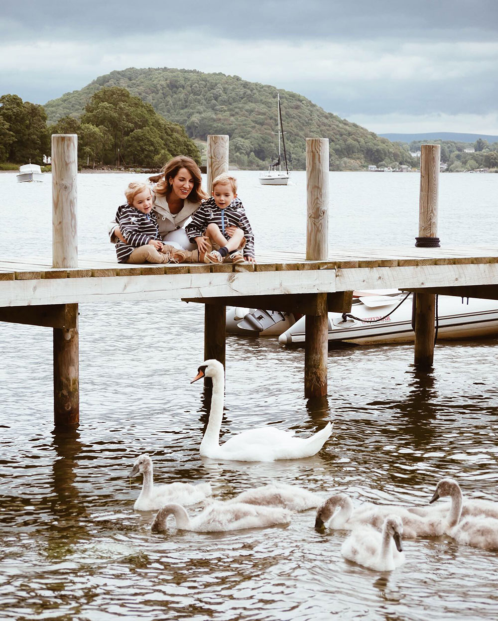 A swan and her sygnets watched by a family on the hotel jetty
