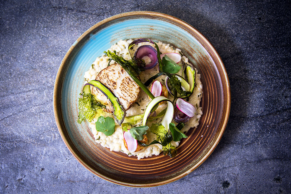 Brown butter poached hake, spring vegetables and herb risotto