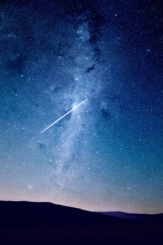 Meteor shower over the hills wit hthe Milky Way in the night sky