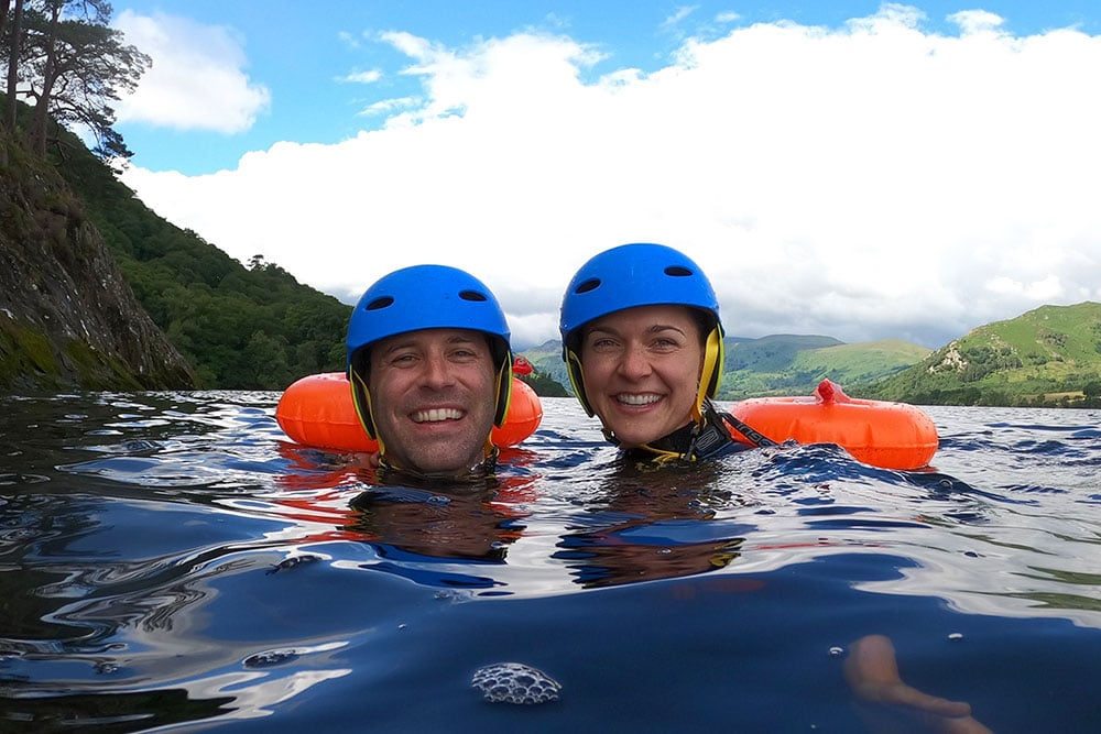 A couple enjoying cold water therapy whilst swimming in Ullswater