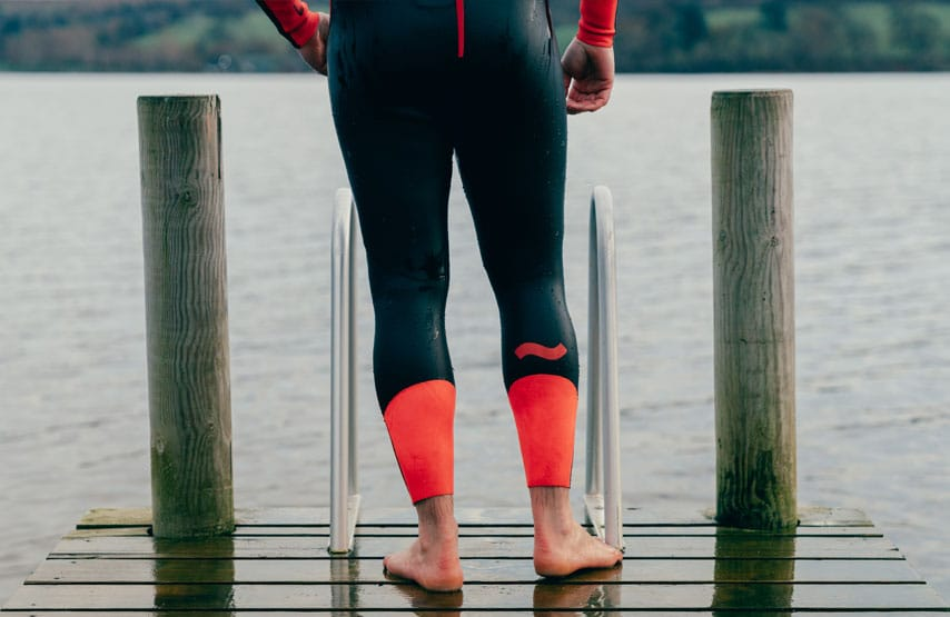 Swimmer wearing a C-Skins swim research wetsuit standing on the hotel jetty
